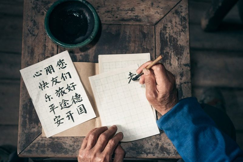 Man writing out Chinese characters.