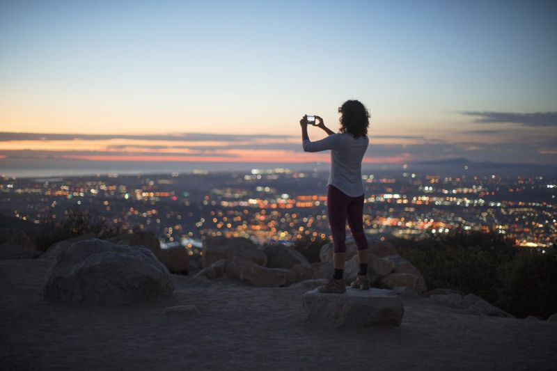 A woman taking a photo of a sunset over a city skyline.