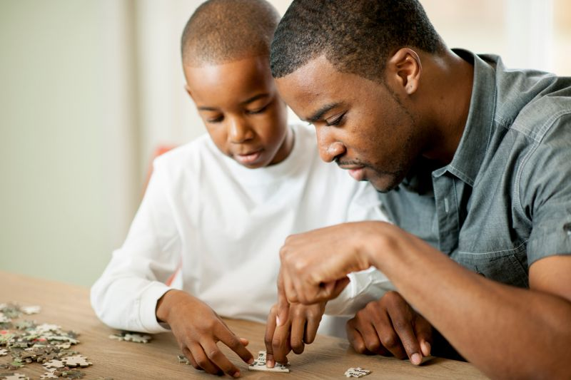 Father and son putting together a puzzle together.