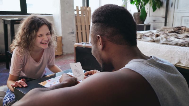 Happy multiethnic couple in pajamas playing the board game on the floor. African man throws dice and puts the card, reads the dice. Caucasian woman laughs. Carefree morning at home together.