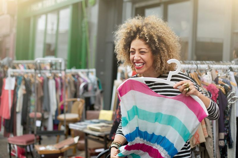 Woman laughing while trying on clothes at market