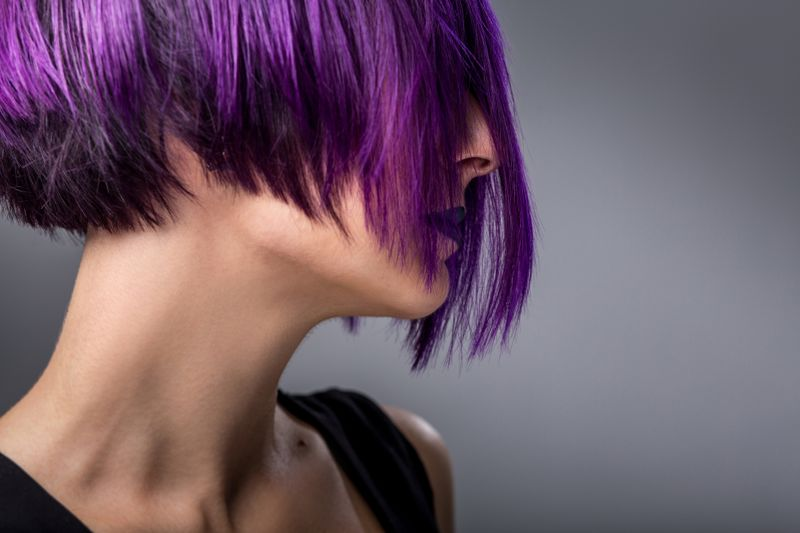 Fashion woman with purple short hair over gray background
