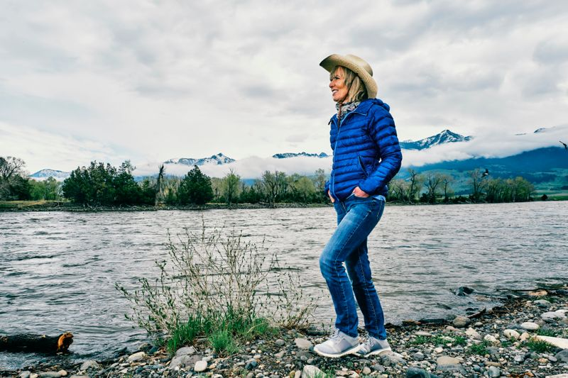 Senior woman relaxing beside the Yellowstone River at Paradise Valley, Montana, USA.