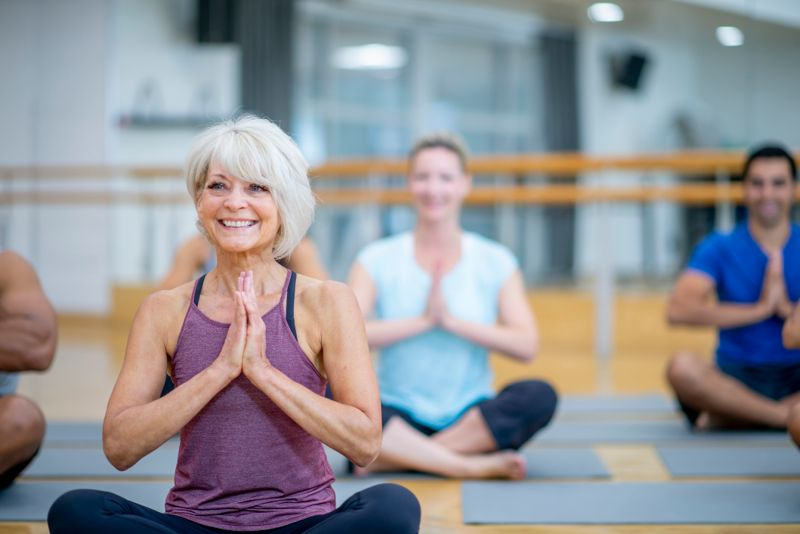 An older Caucasian woman is seen sitting in a gymnasium during a yoga class. She is sitting crossed-legged and in the prayer pose with a smile on her face and enjoying the class.
