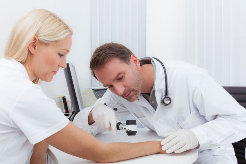 doctor inspecting skin for candida infection