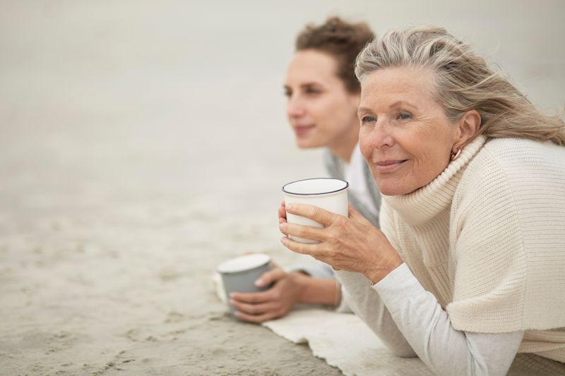 Senior woman and adult daughter drinking coffee on the beach