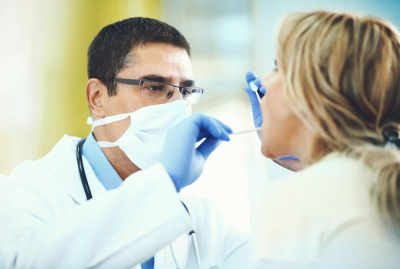 doctor examining mouth tonsils