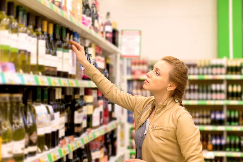 woman buying wine in the supermarket