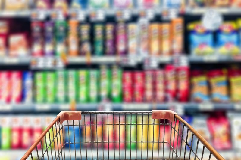 Shopping Cart View in front of abstract blur view of real shopping mall potato chip snack on shelf,