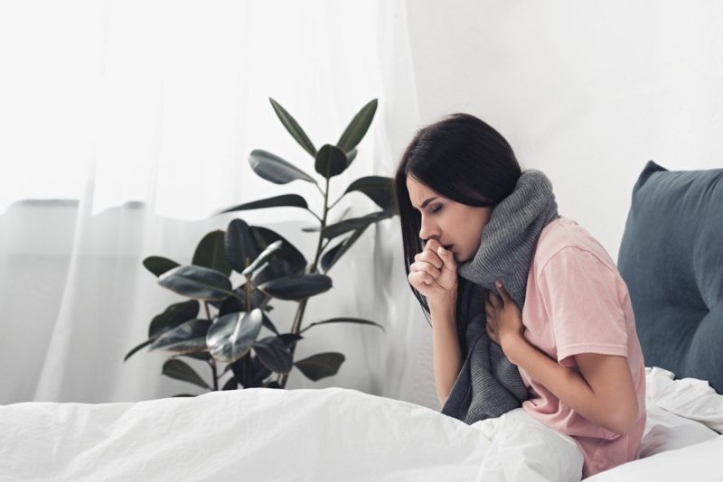 woman coughing bed
