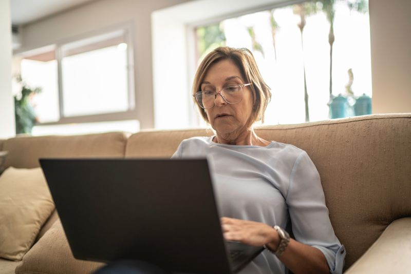 Mature woman using laptop in the living room