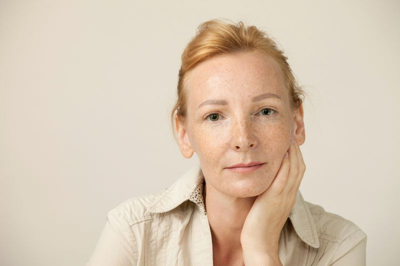 Studio portrait of woman blondes with freckles on beige background