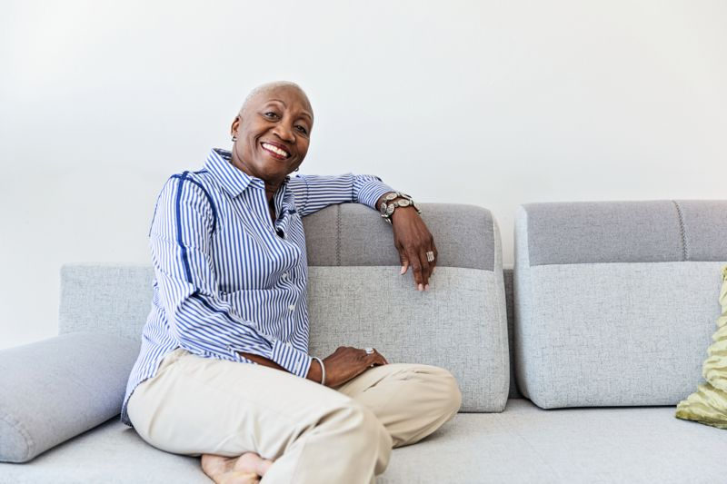 Cheerful senior woman sitting on the couch at home, relaxing. Well dressed and confident.