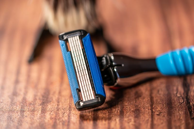Close up of a manual wet razor blade in front of a soft and out of focus shaving brush