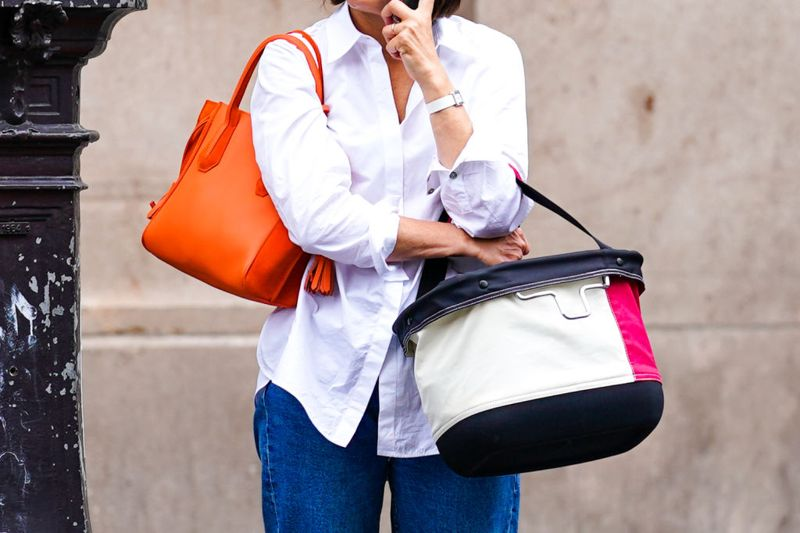 A passerby wears a white shirt, a watch, an orange Celine leather bag, blue jeans, holds a large bag, on July 04, 2020 in Paris, France.