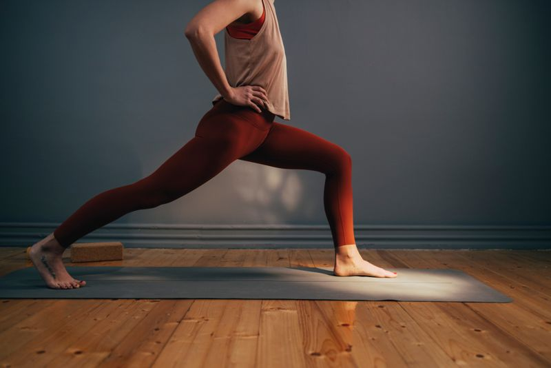 Side view of an anonymous fit Caucasian woman doing a lunge on her gray yoga mat