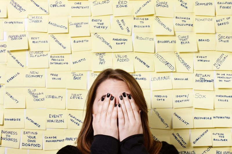 Hands over face, woman hides from excess of business buzzwords