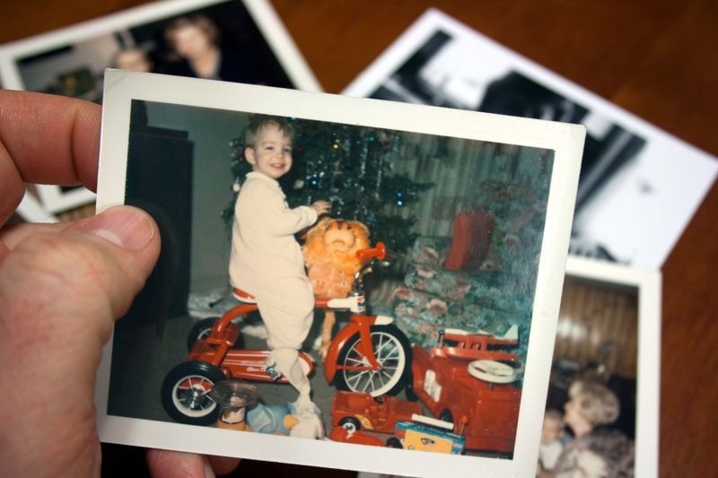 Hand holds Vintage photograph of boy on tricycle at christmas