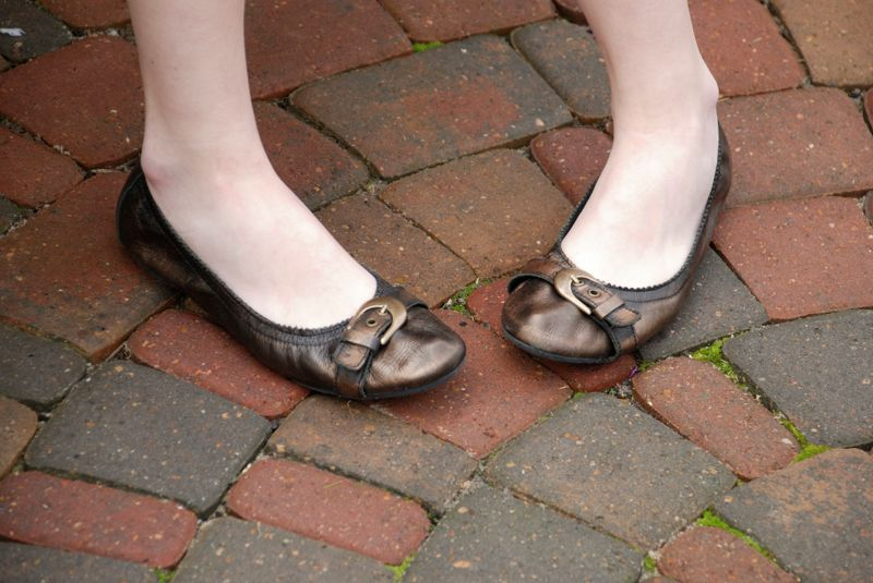 Close up of the feet of a teenaged girl wearing flat shoes with a buckle against brick paving stones