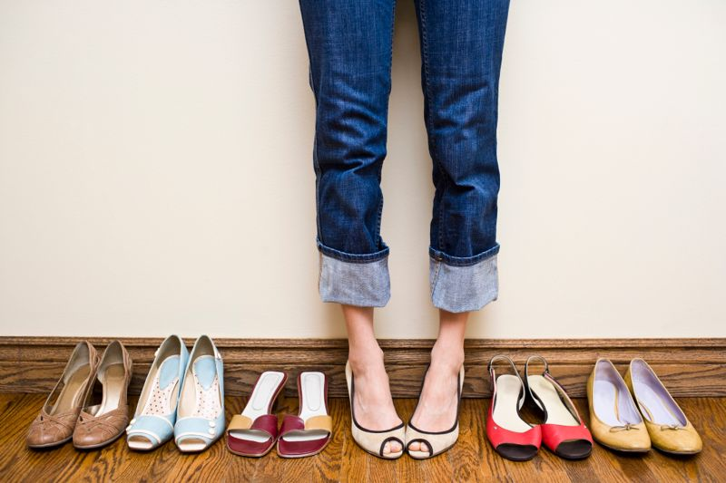 Woman stands in a pair of open toe heels in the middle of a row of shoes showing the concepts of consumerism, individuality, shoe addiction, fashion and shopping