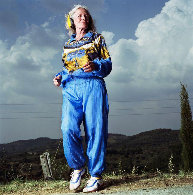 Mature woman wearing head phones jogging on road