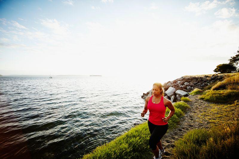 Woman running on path near shoreline at sunset