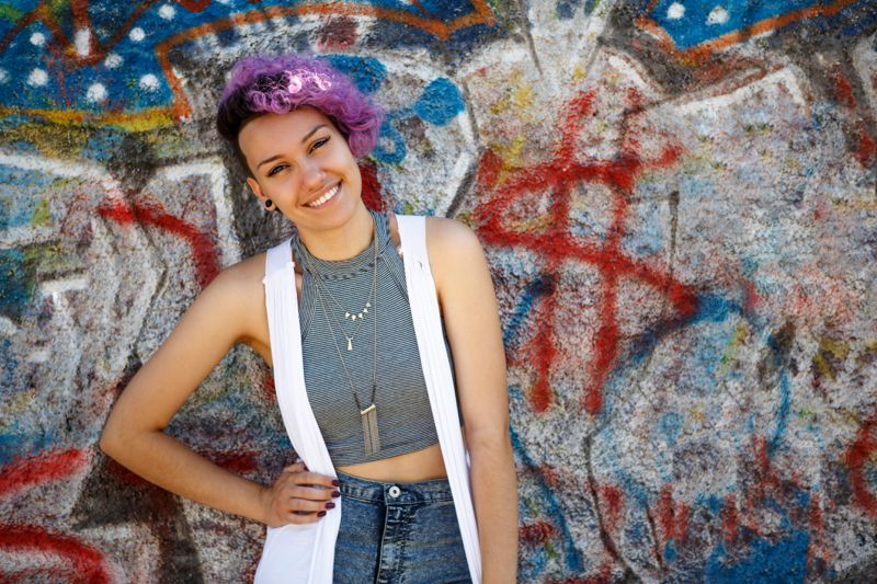 Smiling young hipster girl posing against graffiti wall