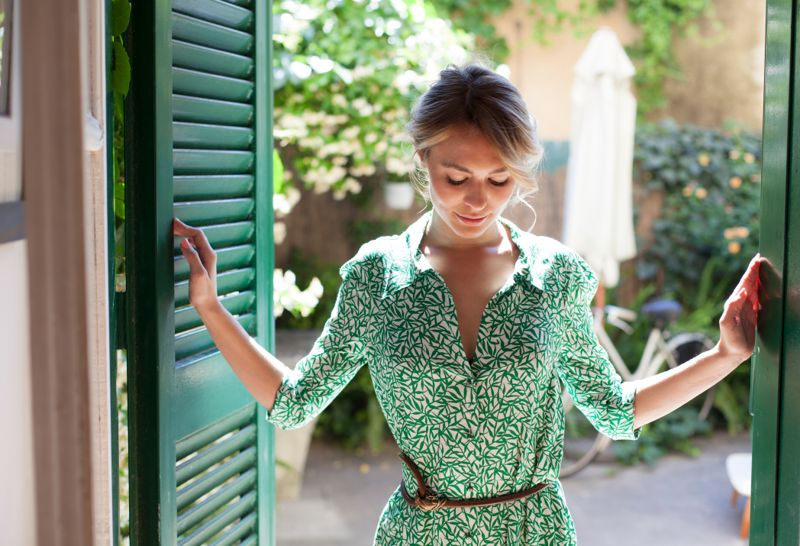 Young woman in green dress stepping inside from the garden