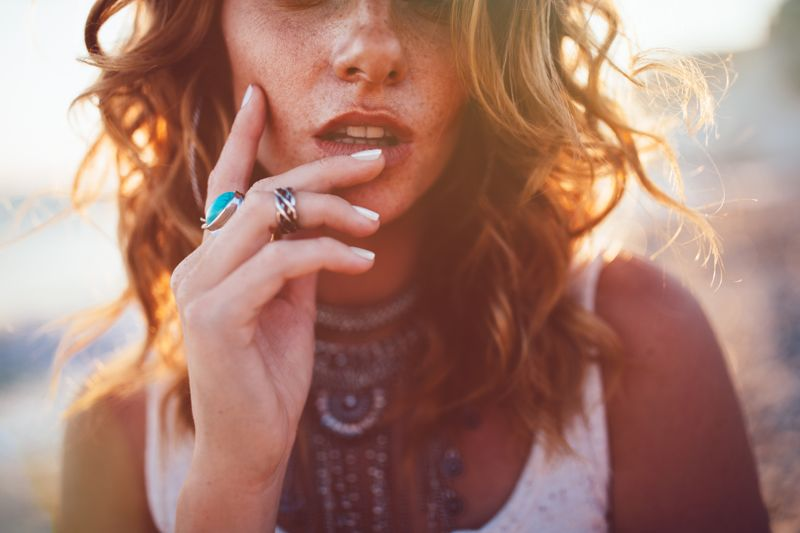 Close-up of bohemian woman with freckles wearing boho style silver turquoise rings and necklaces