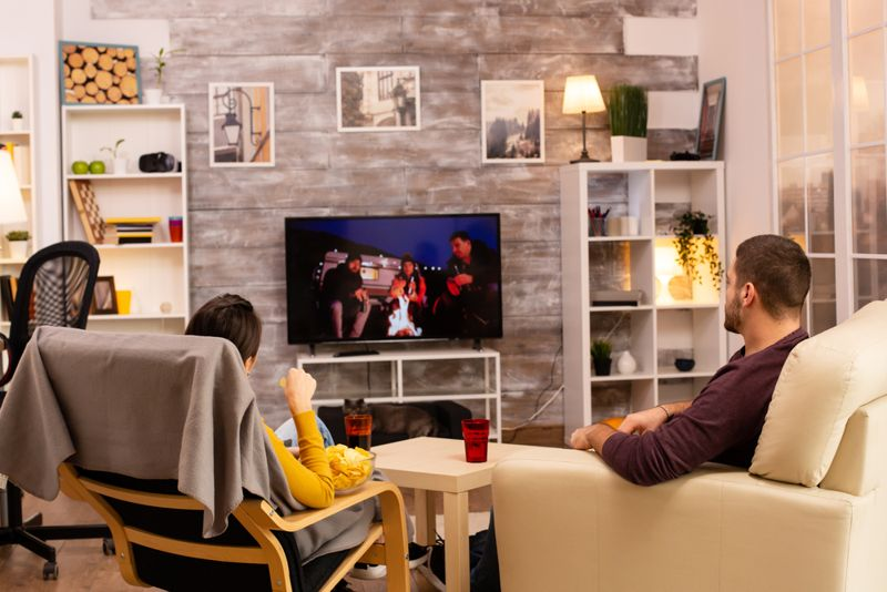 Back view of couple in living room watching a movie on the TV while eating takeaway food