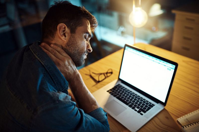 a man on his pc with neck pain