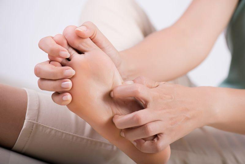 woman scratching foot blister