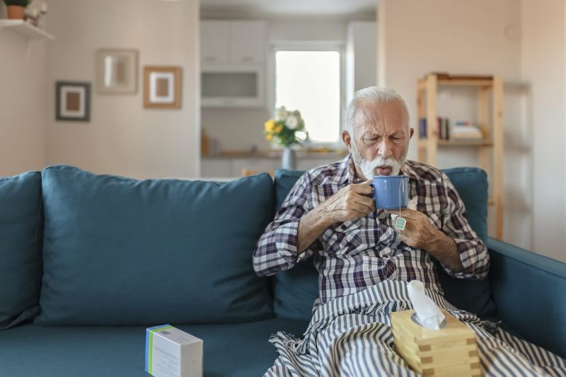 sick man drinking tea