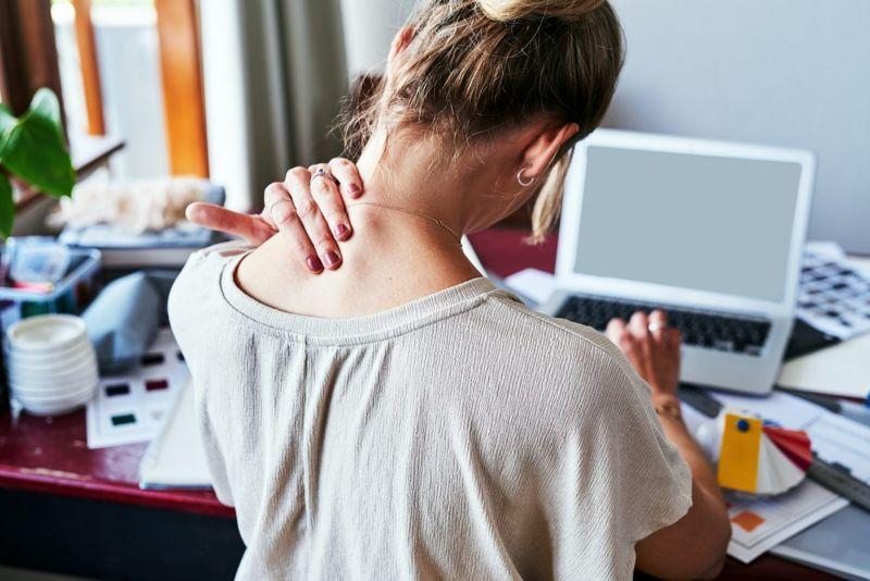a woman rubs her neck