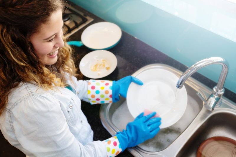 washing dishes in rubber gloves