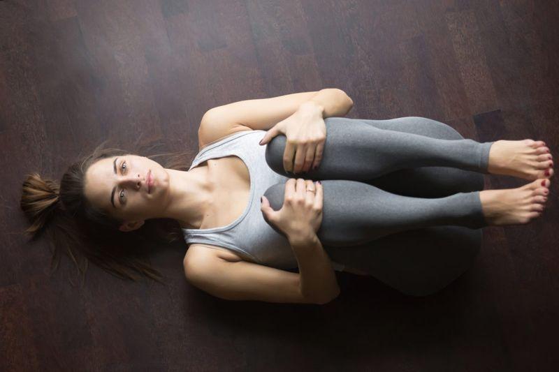Woman performing back flexion stretch