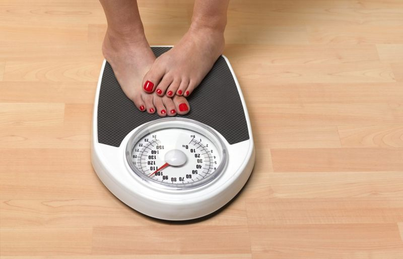 a woman stands on the scale