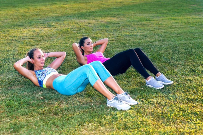 Women performing curl-ups outside