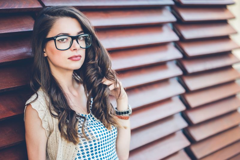 Young woman with glasses enjoying outside in sunny day.