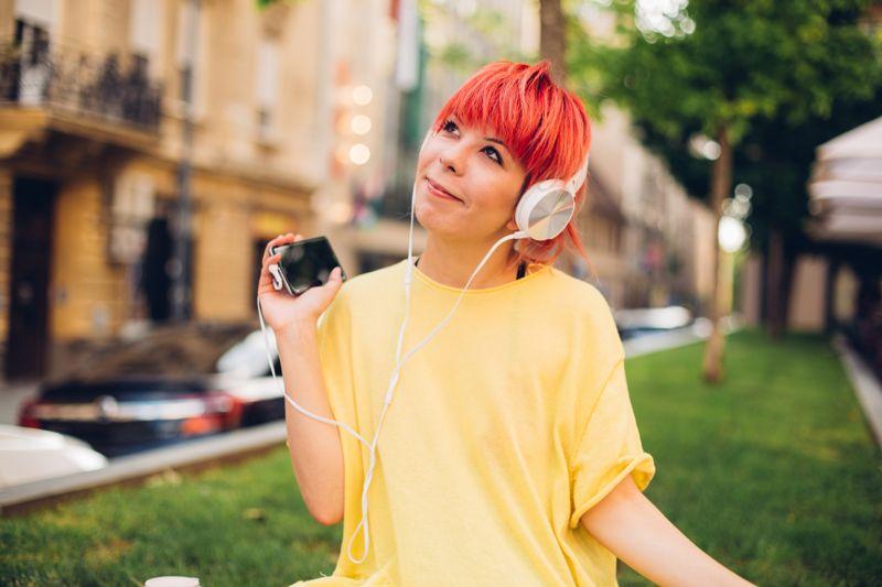 Woman wearing headphones when using smart phone