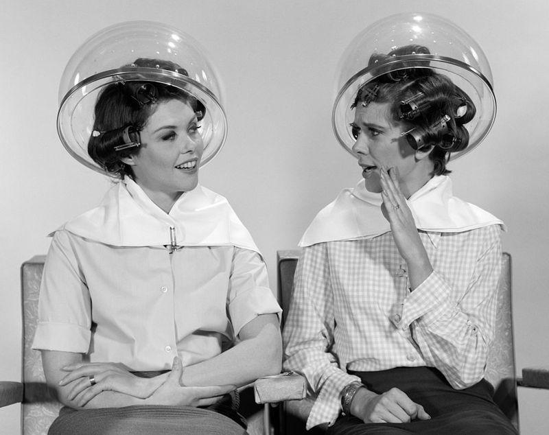 1960s TWO WOMEN SITTING TOGETHER GOSSIPING UNDER HAIRDRESSER HAIR DRYER