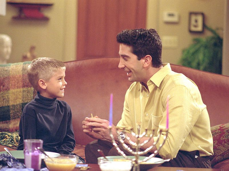 """385848 23: Actors Cole Mitchell Sprouse (Big Daddy) as Ben and David Schwimmer as Ross Geller star in NBC's comedy series """"Friends"""" episode """"The One with the Holiday Armadillo."""" Ross has Ben for the holidays and decides that this season, they will celebrate Chanukah instead of Christmas. (Photo by Warner Bros. Television)"""
