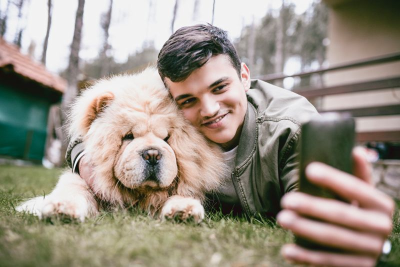 Young Male Taking A Selfie With Pet Chow Chow Dog