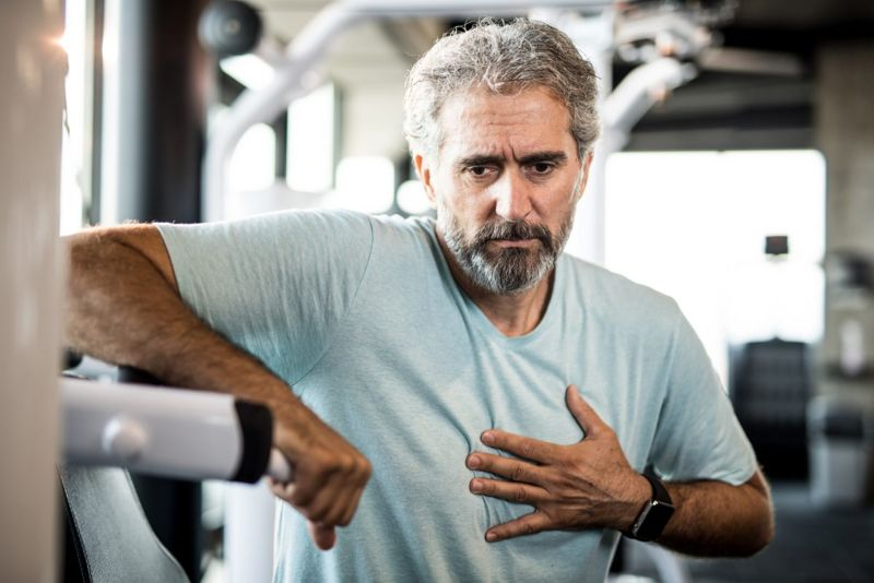 Man holding chest while working out