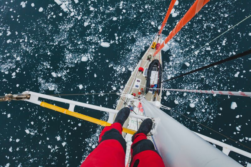 sailing boat in Antarctica, extreme dangerous travel selfie, person feet standing on mast of a yacht with floating ice, top view, adventure
