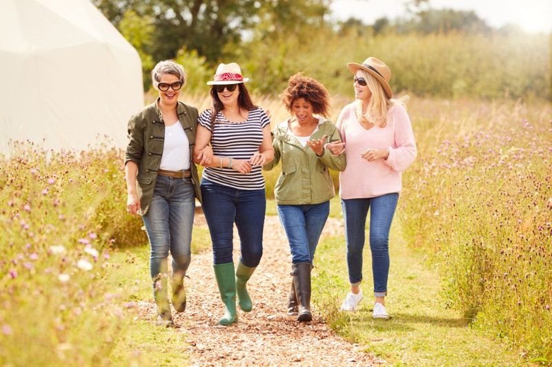 A group of four mature female friends walking along a path. They are all wearing fitted denim jeans. Three of them are wearing fitted t-shirts. Two are wearing fitted jackets. One is wearing a loosely fitting sweater.
