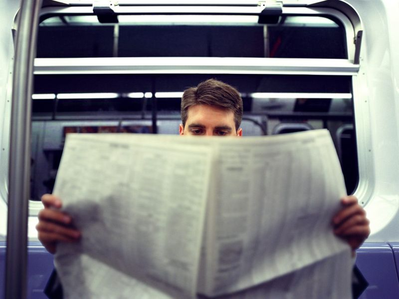 Smart man reading newspaper on train