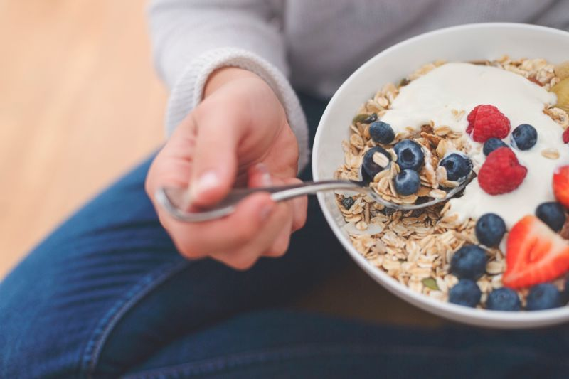 Woman Eating healthy breakfast bowl. It includes strawberries, blueberries, kiwifruit, granola, muesli and yoghurt. Clean eating, dieting, detox, vegetarian food concept. Shot from above