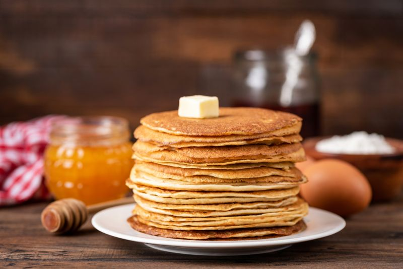 Blini or crepe or thin pancakes stack on wooden table topped with butter. Shrove Tuesday, Maslenitsa holiday concept. Rustic style breakfast