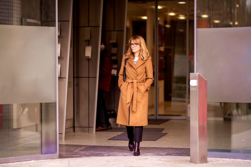 Full length shot of pretty mature woman wearing beige coat and bag while walking out of the bank building.
